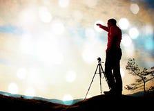 影片五谷 有三脚架的自然摄影师在峭壁和认为 梦想的老保守风景,在一美好的vall的橙色有薄雾的日出 库存照片