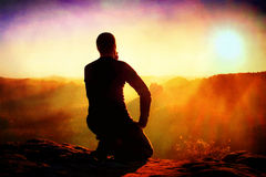 影片五谷 黑运动服的Sportsmann远足者坐山上面并且采取与观看的休息下来对早晨谷 库存照片