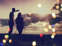影片作用 享受奇妙片刻的夫妇在日落期间 年轻对峰顶的远足者 免版税库存图片