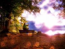 影片作用 单独人腿坐在一个天蓝色的山湖旁边的长凳 人放松并且观看阿尔卑斯高山在湖mir上的 免版税库存图片