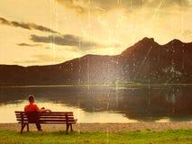 影片作用 单独人腿坐在一个天蓝色的山湖旁边的长凳 人放松并且观看阿尔卑斯高山在湖mir上的 库存图片