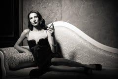 影片努瓦尔样式:说谎在沙发和抽烟的香烟的危险典雅的少妇 黑色白色 图库摄影