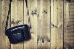 影片照相机的皮革盒在木背景 免版税库存照片