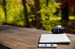 影片照相机膝上型计算机和智能手机在户外表Copyspace上 免版税库存图片
