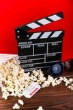 影片观看 玉米花、clapperboard和玻璃在木和红色背景 免版税图库摄影