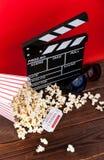 影片观看 玉米花、clapperboard和玻璃在木和红色背景 库存图片