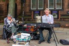 彻斯特,英国- 2019年6月26日:年长卖艺人弹键盘和萨克斯管游人的 免版税库存照片