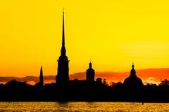 彼得和保罗堡垒黑剪影在圣彼德堡,落日光芒的俄罗斯  图库摄影