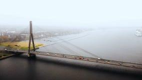 往充分美丽的老索桥的寄生虫飞行在史诗道加瓦河的汽车通行在里加在灰色有雾的秋天天 影视素材