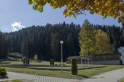 往公园的秋季看法有自然森林和新的露天幼儿园的, Rila山 免版税库存图片