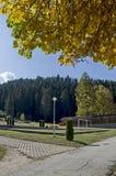 往公园的秋季看法有自然森林和新的露天幼儿园的, Rila山 库存图片