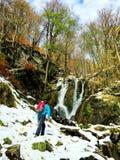 去往在秋天季节的瀑布的远足者 免版税库存图片