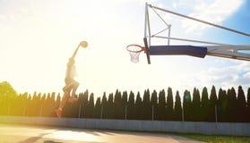 往外缘的一次年轻蓝球运动员飞行灌篮的 库存照片