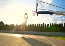 往外缘的一次年轻蓝球运动员飞行灌篮的 库存图片