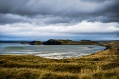 往山的日落视图冰岛与草水和云彩 免版税图库摄影