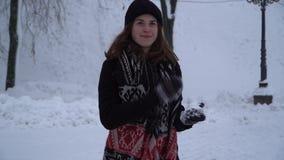 往照相机投掷的雪球的俏丽的年轻女人奔跑在积雪的公园 冬天外套的女孩和帽子有 股票录像