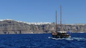 往Fira镇的小船标题在圣托里尼 库存图片