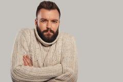很冷!保持胳膊的温暖的毛线衣的英俊的年轻人横渡 免版税库存照片