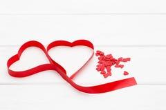 很多一点红色心脏和一条红色丝带以心脏的形式在白色木背景 免版税库存照片