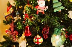 很多事在圣诞树垂悬:圣诞老人、响铃和球,姜饼人和棒棒糖,雪人 免版税库存照片