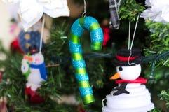 很多事在圣诞树垂悬:圣诞老人、响铃和球,姜饼人和棒棒糖,雪人 库存图片