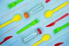 很多五颜六色的一次性碗筷例如叉子,刀子,匙子,秸杆,在浅兰的背景的瓶 r 免版税库存图片
