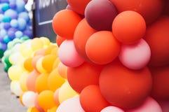 很多多彩多姿的气球,橙色和红色,自豪感节日 免版税库存照片