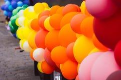 很多多彩多姿的气球,橙色和黄色,自豪感节日 免版税图库摄影