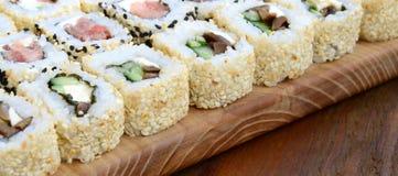 很多寿司卷特写镜头用不同的装填的说谎木表面上 煮熟的经典日本食物宏观射击与 图库摄影