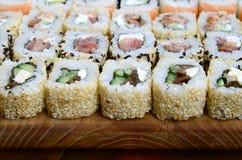 很多寿司卷特写镜头用不同的装填的说谎木表面上 煮熟的经典日本食物宏观射击与 库存照片