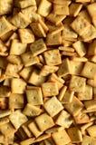 很多小曲奇饼方形形状 一个黄色盐薄脆饼干的样式 与盐味的pastr的背景图象 库存图片