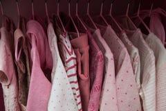 很多桃红色儿童` s在挂衣架穿衣 儿童与衣裳的` s衣橱 免版税库存照片