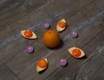 很多灼烧的橙色和紫色圆的蜡烛用桔子 库存图片