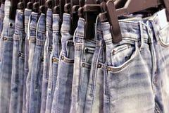 很多牛仔裤浅兰在挂衣架在商店 免版税库存照片