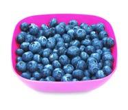 很多甜蓝莓,隔绝在白色背景 在一块明亮的桃红色板材的夏天莓果 有机和自然果子 免版税库存图片