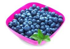 很多甜蓝莓,隔绝在白色背景 在一块明亮的桃红色板材的夏天莓果 有机和自然果子 图库摄影