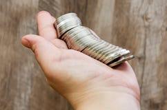 很多硬币在女性手上 免版税库存图片