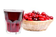 很多红色,成熟樱桃在一个柳条筐和与一杯在白色背景的樱桃汁 查出 图库摄影