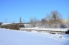 很多老路轨和睡眠者在一个铁路仓库里被堆积在冬天 更新一条破旧铁路轨道的概念 库存照片