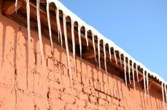 很多长的冰柱垂悬在一个红砖大厦的屋顶下 图库摄影