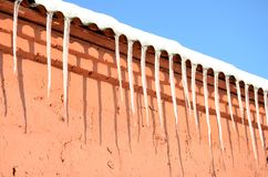 很多长的冰柱垂悬在一个红砖大厦的屋顶下 库存图片