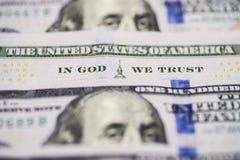 很多100张美元票据钞票 在神我们在神信任比尔一百个美元特写镜头词组我们信任 免版税库存照片