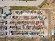 很大数量的铁车库鸟瞰图汽车的有站立接近彼此的色的屋顶的在被操刀的路附近 免版税库存图片