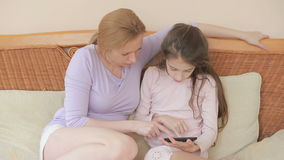 很好一个美丽的母亲和她小的女儿谈话,母亲拿着一种片剂并且教她的女儿 股票录像