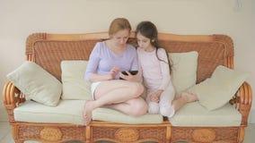 很好一个美丽的母亲和她小的女儿谈话,母亲拿着一种片剂并且教她的女儿 股票视频