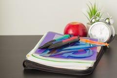 很快到学校、学校笔记本和文具、闹钟和苹果计算机在桌,学校的起点的概念上 免版税图库摄影