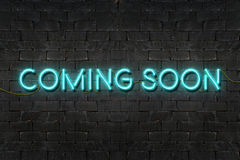 很快来的` `霓虹灯广告发光在黑砖墙的,企业概念 皇族释放例证