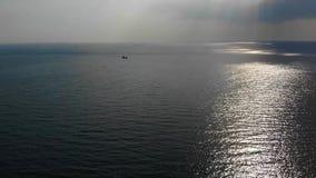 很远船的好的鸟瞰图,发光通过云彩的美丽的太阳