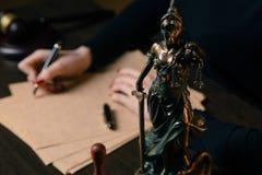 律师与合同纸和木惊堂木一起使用在tabel在法庭 法官和法律,律师,法院法官, 免版税库存图片