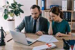 律师和哭泣的客户谈论合同在工作场所与膝上型计算机 免版税库存照片